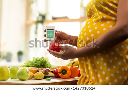 Nitrate meter. Expectant mother in a beautiful dress checking the level of nitrates in a tomato.