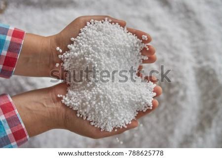 Nitrogen fertilizers or urea fertilizer in farmer hand. blurwhite fertilizer background.
