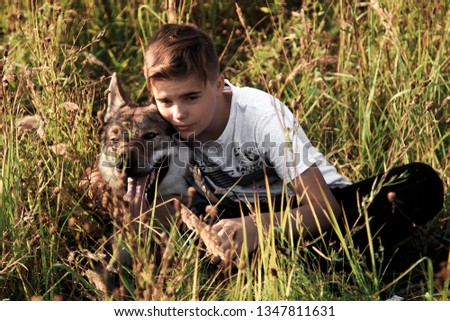Nizhny Novgorod city,Nizhny Novgorod region,Russian Federation. 09.13.2018.Editorial. Teenage boy walking in the field with a wild wolf. The friendship of a boy and a wild beast. The loyalty of a wolf #1347811631