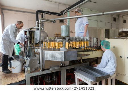 NIZHNY TAGIL, RUSSIA - APRIL 24, 2015: Maintenance of automatic production line of ice cream. Man repairing feeding formula. Women are laid wooden popsicle sticks