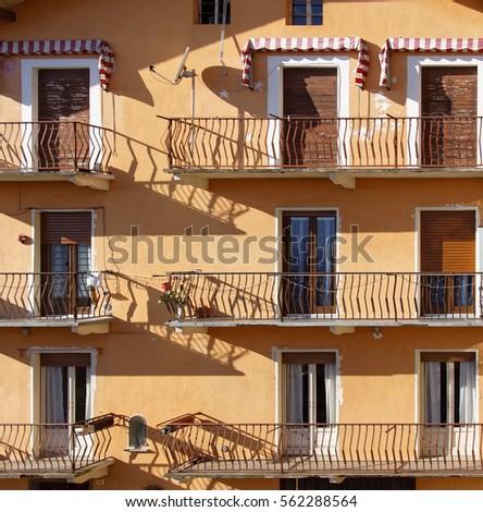 Nne doors, sixbalconies, orange Italian facade with blinds Stock fotó ©