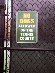 no dogs allowed sign on public tennis courts