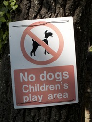 No dogs childrens play area warning sign mounted on tree trunk