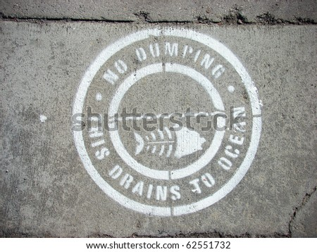 no dumping drains to ocean sign on concrete sidewalk