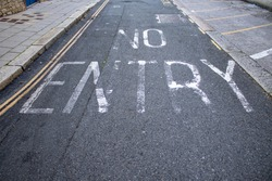 No Entry painted on road with faded white paint