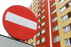 No entry road sign. Living area one way road. Car traffic prohibited. Block of flats in the background. Road sign isolated. Warning no entry zone. Drive in forbidden.