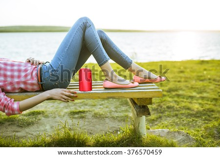Stock Photo No face caucasian girl, Woman lie on bench against green fresh grass, sea and sunset sky background . Female on nature spring backdrop. Slim legs in jeans