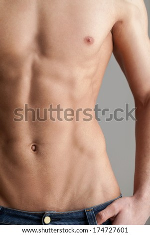 No fat! Cropped image of muscular man standing isolated on grey background