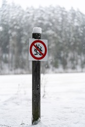 No fire making sign located near the Ahja river in Taevaskoja region of Estonia. Frozen river on the background. Winterwonder land all around. Area where you cant make camp fire. Black and white