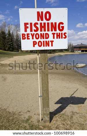No Fishing Beyond this Point sign on a sandy beach with blue sky background