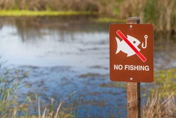 No fishing sign in front of a pond.