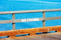 No Fishing sign on wooden railing of wharf. Blue ocean water background