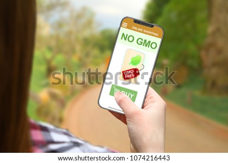 No GMO concept, girl with frameless phone on blurred nature background #1074216443