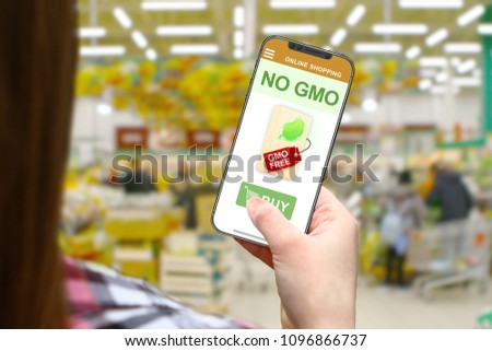 No GMO concept, girl with frameless phone on blurred shop background #1096866737