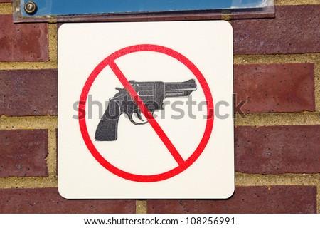No guns sign seen on the brick wall