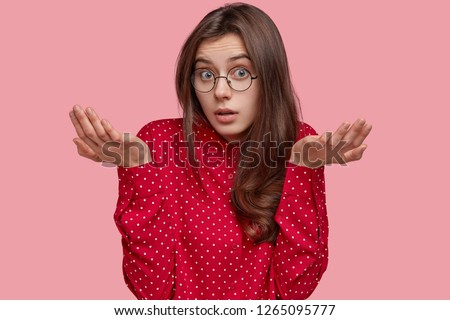 No idea. Unaware careless young woman spreads hands in clueless gesture, looks doubtfully at camera, makes decision, dressed in polka dot blouse, isolated over pink studio wall, has raised arms