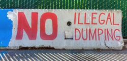 NO ILLEGAL DUMPING warning sign painted on cement barricade.