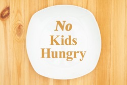 No Kids Hungry message on white empty plate on a wood table
