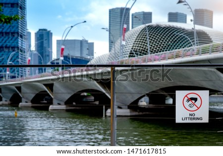 No littering sign on wire fence beside the river in downtown with skyscraper business building. Signs for not throwing garbage into the river. Signs for do not dumping garbage in Singapore city. #1471617815