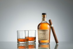NO LOGOS OR TRADEMARKS!  SELF MADE LABELS! close up view of cigar, bottle of whiskey and a glass aside ongrey back.