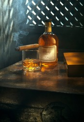 NO LOGOS OR TRADEMARKS!  SELF MADE LABELS! close up view of cigar, bottle of whiskey and glass aside ongrey back.