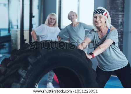 No more boundaries. Selective focus on a sporty retired lady looking into the camera with a smile on her face while training with a heavy wheel at a gym. #1051223951