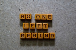 No One Left Behind on wooden cubes. On table background