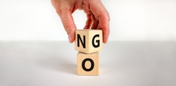 No or go symbol. Businessman turns a cube, changes the word 'no' to 'go'. Beautiful white background. Copy space. Business, motivation and no or go concept.