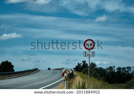 No overtaking sign. Road sign on the road in front of the bridge against the blue cloudy sky . High quality photo Сток-фото ©