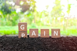 No pain no gain concept. Hand changing pain word to gain in wooden blocks on natural background.