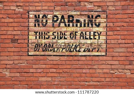 No parking, antique sign painted on a brick wall