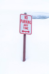 No Parking Anytime signage with arrow isolated against white snow in winter