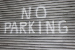 No Parking painted on metal wall background