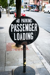 No Parking - Passenger Loading Street Sign on side of street in busy downtown San Francisco California