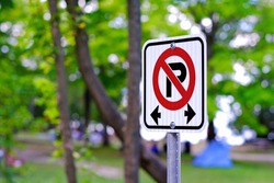 No parking sign inside park against blurred nature green trees and people background.