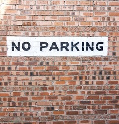 No Parking sign on Brick wall background, texture
