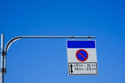 No parking sign with arrow hanging on blue sky