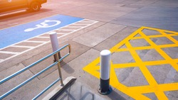 No parking sign with disabled wheelchair and railing on concrete ground surface in parking lot of public restroom area at petrol station