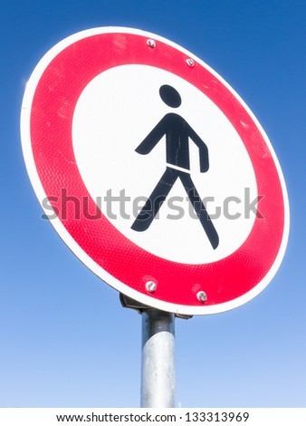 no pedestrian sign  in front of blue sky