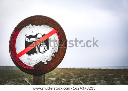 Photo of No photography allowed  old sign on the wooden post by the military base with sea nearby surounded by the fence. Restricted areas in Romania.Background image with free space.