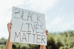 No racism End racism.Crowd of protesters people on street.black woman raised hands showing sign black lives matter for revolution protest.Black Lives Matter.Justice in USA.