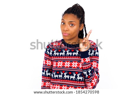 No sign gesture. Closeup portrait unhappy Young beautiful African American woman wearing Christmas sweater against white wall, raising fore finger up saying no. Negative emotions facial expressions.
