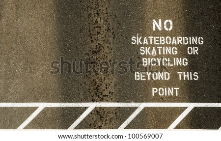 No skateboarding skating or bicycles beyond this point, sign painted on footpath