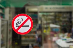 No smoking area sign at the glass door of drug store.