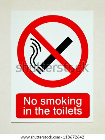 no smoking in the toilets sign on white wall - stock photo