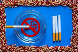 no smoking sign in a glass ashtray with a cigarette in it and cigarettes in a row next to, in a frame of broken matchsticks, on blue background