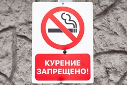 No smoking sign in Russian against a gray stone background.