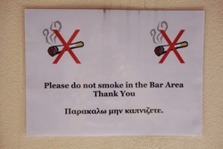 No smoking sign written in English and Greek with graphic