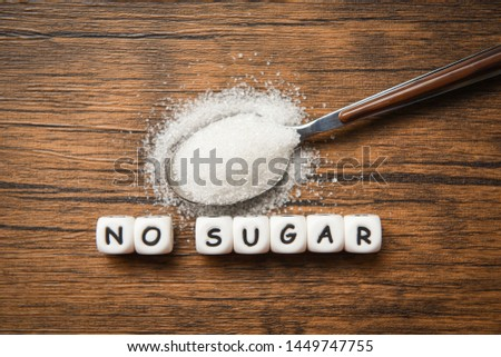 no sugar text blocks with white sugar on spoon wooden background / suggesting dieting and eat less sugar for health concept