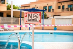 No swimming sign. Pool under closure. Consequences of self isolation during coronavirus times. Restrictions for any group activities. Abandoned swimming pool at the time of epidemic. Health measures.